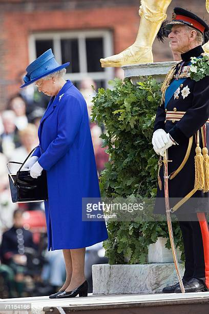 Queen Elizabeth II, accompanied by Prince Philip, the Duke of Edinburgh, looks in her handbag at the Founder's Day Parade at the Royal Hospital...