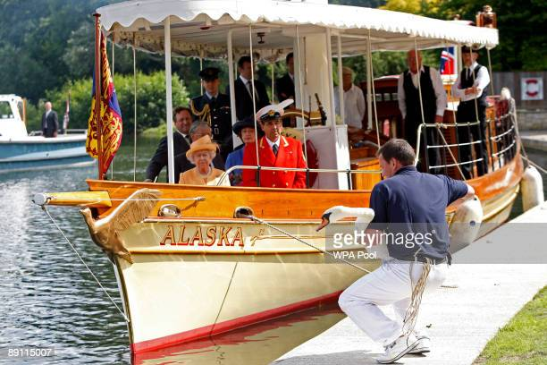 Queen Elizabeth II accompanied by Swan Marker David Barber watches from the steam launch 'Alaska' as a swan upper places a swan back into the river...