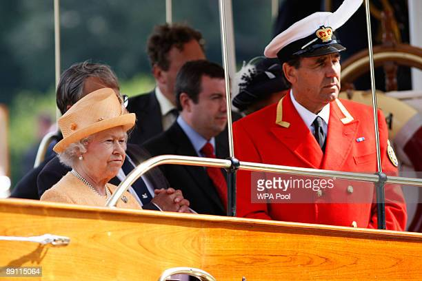 Queen Elizabeth II accompanied by Swan Marker David Barker watches the swan upping census from the steam launch 'Alaska' on the River Thames on July...