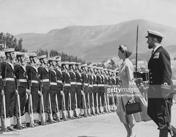 Queen Elizabeth II, accompanied by the Guard Commander inspecting a Guard of Honour at Prince's Wharf, Hobart, during the Commonwealth tour of...