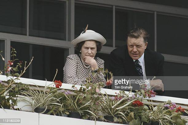 Queen Elizabeth II alongside Sir Michael Oswald manager of the Royal Stud at Epsom racecourse for the Derby meeting in Epsom Surrey England Great...