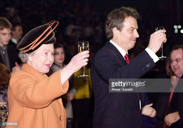 Queen Elizabeth II and British Prime Minister Tony Blair raise their glasses as midnight strikes during the Opening Celebrations on December 31, 1999...