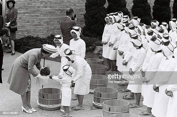 Queen Elizabeth II and Duke of Edinburgh are seen off by female divers after inspecting a pearl factory during their visit to Japan on May 11 1975 in...