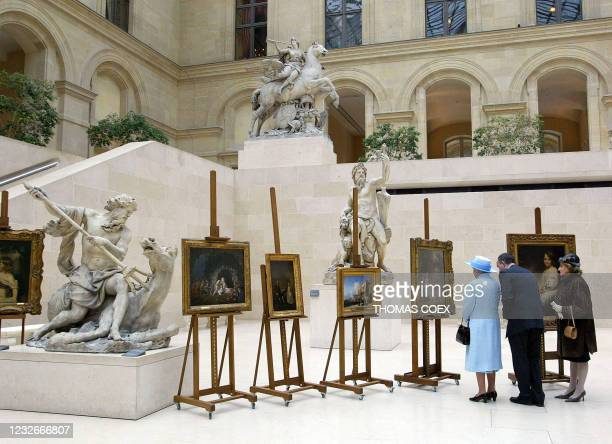 Queen Elizabeth II and French First Lady Bernadette Chirac listen 06 April 2004 to Louvre curator Olivier Meslay during their visit of 18th century...