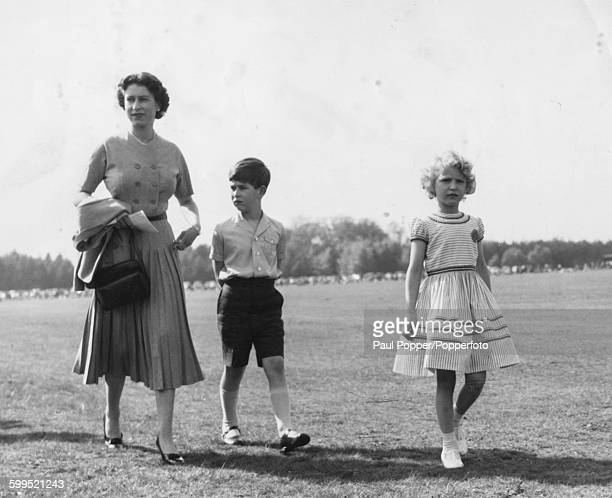 Queen Elizabeth II and her children Prince Charles and Princess Anne walk together through the grounds of Windsor Great Park after watching a polo...