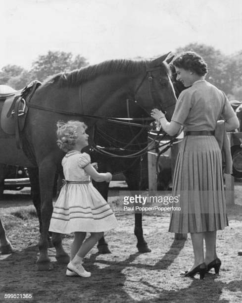 Queen Elizabeth II and her daughter Princess Anne share a joke as they visit the pony paddock following a polo match on Smith's Lawn by Windsor Great...