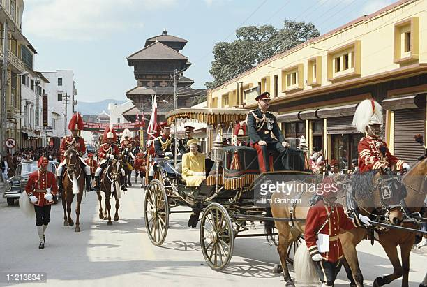 Queen Elizabeth II and her Equerry Major Hugh Lindsay ride a horsedrawn carriage on the Queen's arrival for a State Visit to Nepal 17 February 1986