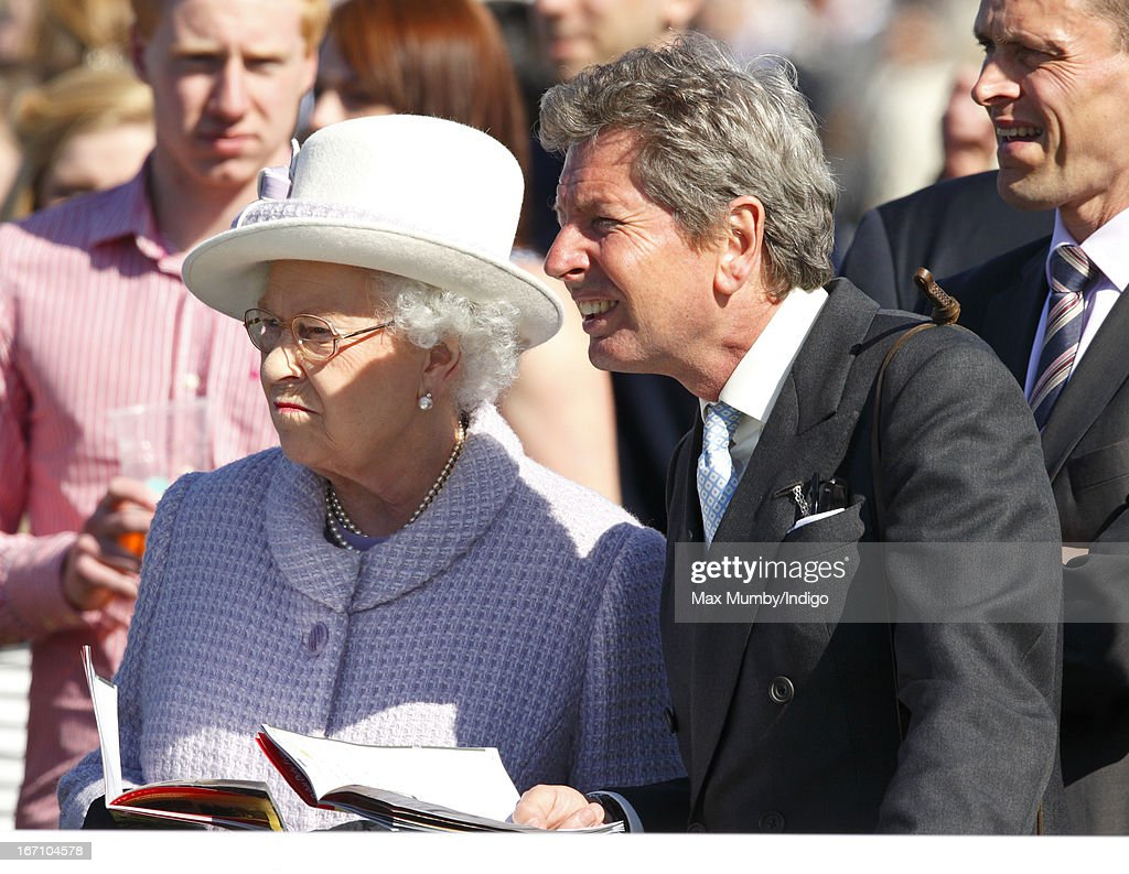 Queen Elizabeth II and her racing manager John Warren watch the horses in the parade ring as they attend the New to Racing Day at Newbury Racecourse on April 20, 2013 in Newbury, England.
