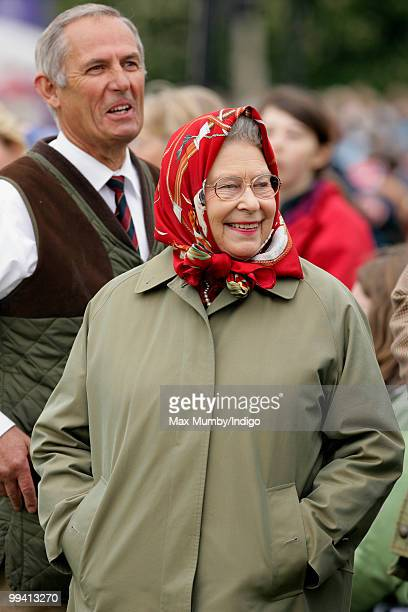 Queen Elizabeth II and her stud groom Terry Pendry watch her horse 'Stardust III' compete in the 'Ladies Side Saddle' class during day 3 of the Royal...