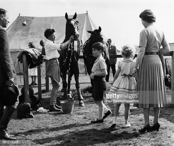 Queen Elizabeth II and her young children Princess Anne and Prince Charles visit the pony paddock after watching the Duke of Edinburgh take part in a...