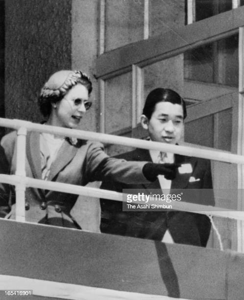 Queen Elizabeth II and Japan's Crown Prince Akihito are seen in the royal box at the Epsom Downs Racecourse on June 6 1953 in Epsom England Crown...