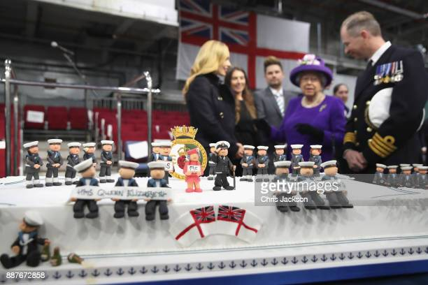 Queen Elizabeth II and Katherine Jenkins look at a cake made by David Duncan during the Commissioning Ceremony of HMS Queen Elizabeth at HM Naval...