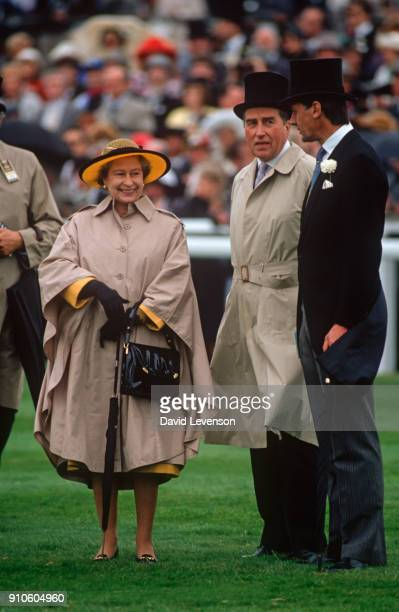 Queen Elizabeth II and Lord Porchester watching the horses in the Parade Ring on Derby Day on June 6 1990 at Epsom racecourse in Epsom Surrey England