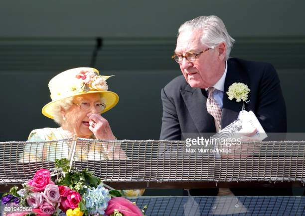 Queen Elizabeth II and Lord Samuel Vestey watch the racing as they attend Derby Day during the Investec Derby Festival at Epsom Racecourse on June 3,...