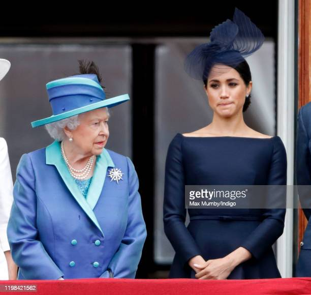 Queen Elizabeth II and Meghan, Duchess of Sussex watch a flypast to mark the centenary of the Royal Air Force from the balcony of Buckingham Palace...