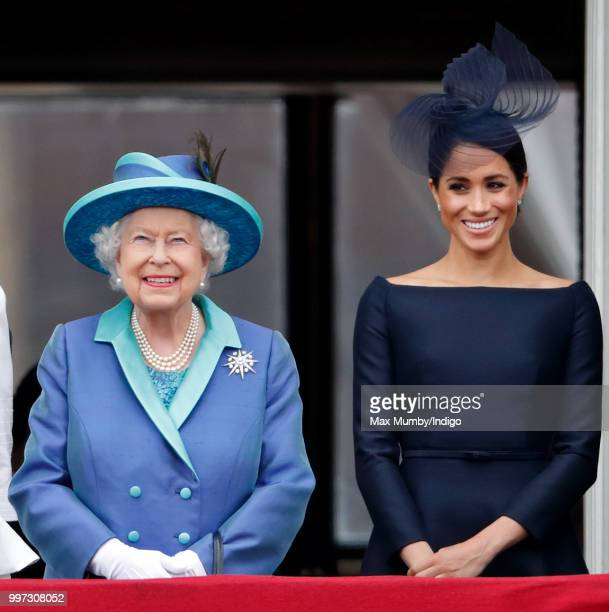 Queen Elizabeth II and Meghan Duchess of Sussex watch a flypast to mark the centenary of the Royal Air Force from the balcony of Buckingham Palace on...