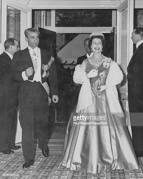 Queen Elizabeth II and Mohammad Reza Pahlavi Shah of Persia wearing formal dress as they arrive for a dinner at the Iranian Embassy in Princes Gate...