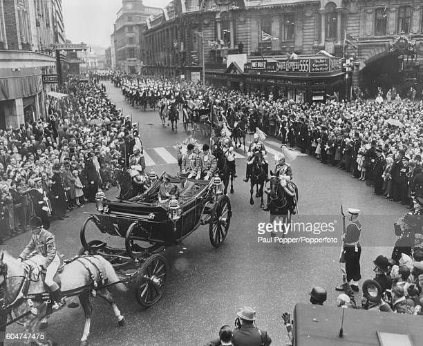 Queen Elizabeth II and President Charles de Gaulle of France ride together in an open Landau carriage past crowds of spectators as they travel from...