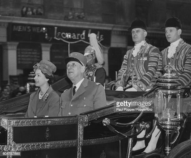 Queen Elizabeth II and President Charles de Gaulle of France ride together in an open Landau carriage along Victoria Street from Victoria Station to...