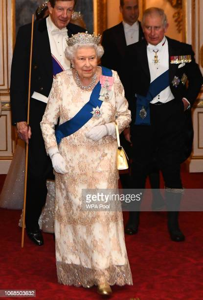 Queen Elizabeth II and Prince Charles Prince of Wales greet guests at an evening reception for members of the Diplomatic Corps at Buckingham Palace...