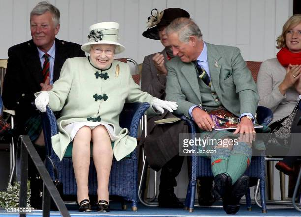 Queen Elizabeth II and Prince Charles Prince of Wales laugh as they watch the tugofwar during the Braemar Highland Games at The Princess Royal and...