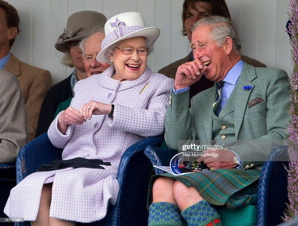 Queen Elizabeth II and Prince Charles, Prince of Wales laugh whilst watching the children's sack race as they attend the 2012 Braemar Highland Gathering at The Princess Royal & Duke of Fife Memorial Park on September 1, 2012 in Braemar, Scotland.