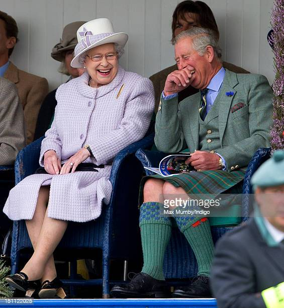 Queen Elizabeth II and Prince Charles Prince of Wales laugh whilst watching the children's sack race as they attend the 2012 Braemar Highland...