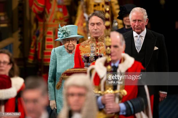Queen Elizabeth II and Prince Charles, Prince of Wales walk through the Royal Gallery ahead of the state opening of parliament at the Houses of...