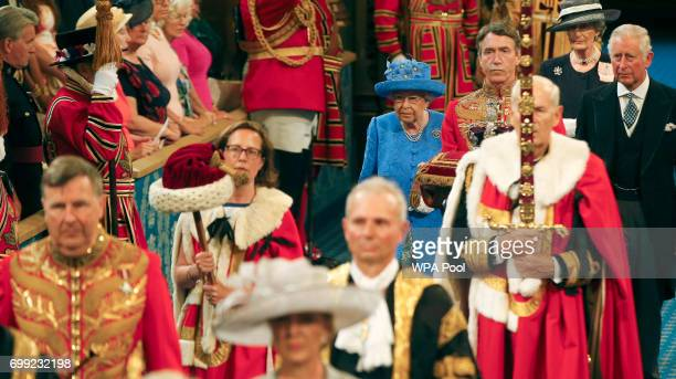 Queen Elizabeth II and Prince Charles Prince of Wales walk through the Royal Gallery prior to the Queen's Speech during the State Opening of...
