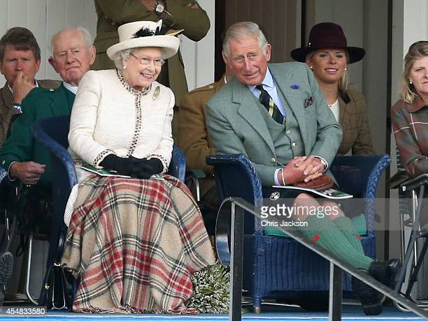 Queen Elizabeth II and Prince Charles Prince of Wales watch the action during the Braemar Highland Games on September 6 2014 in Braemar Scotland The...