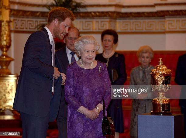 Queen Elizabeth II and Prince Harry looks at the Webb Ellis Cup on a plinth during a reception to mark the Rugby World Cup 2015 at Buckingham Palace...