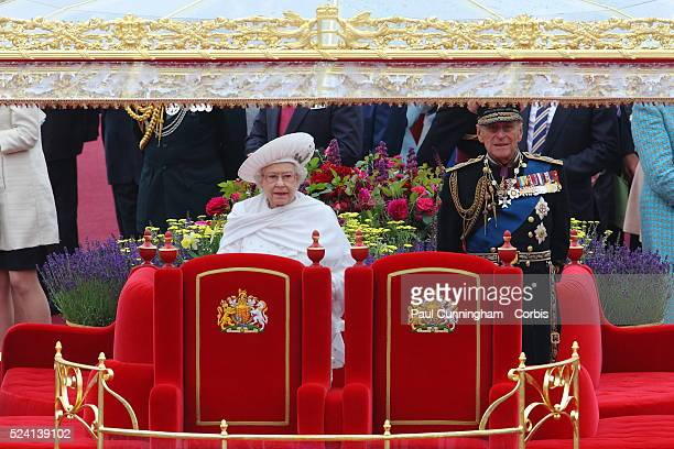 Queen Elizabeth II and Prince Philip aboard the Royal Barge Spirit of Chartwell heads the historic flotilla of 1000 boats along the Thames river past...