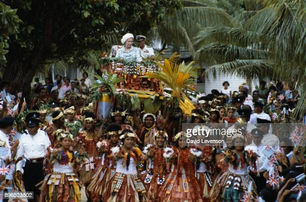Queen Elizabeth II and Prince Philip are carried on local canoes to the Vaiaku maneapa of Funfuti in Tuvalu on October 26 1982 during the Royal Tour...