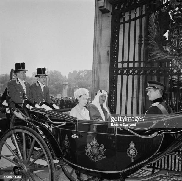 Queen Elizabeth II and Prince Philip arrive back at Buckingham Palace by coach with King Faisal of Saudi Arabia during his official visit to London,...