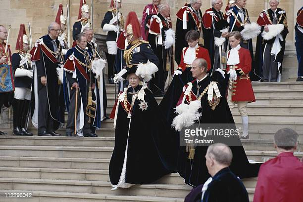Queen Elizabeth II and Prince Philip, both wearing ceremonial robes, in the the grounds of Windsor Castle on their way to St George's Chapel for the...