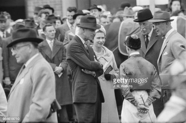Queen Elizabeth II and Prince Philip chatting with jockey R Elliott Charles Moore and Tom Mason at Newbury Racecourse UK 27th May 1961