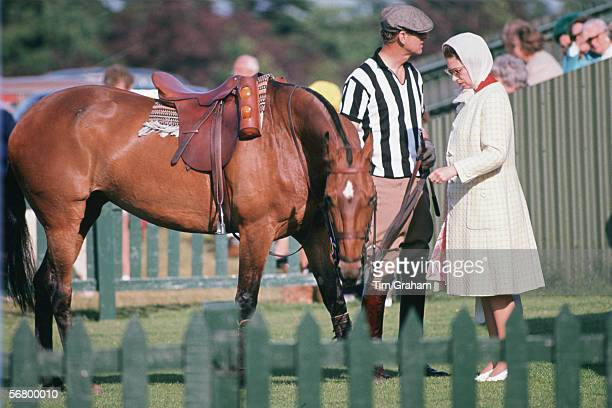 Queen Elizabeth II and Prince Philip, dressed as an umpire, at Smith's Lawn Polo Cub.