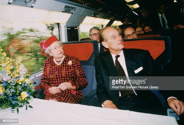 Queen Elizabeth II and Prince Philip Duke of Edinburgh aboard Eurostar on the inauguration of the Eurotunnel Sitting behind them is former Prime...