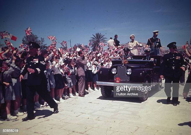 Queen Elizabeth II and Prince Philip Duke of Edinburgh are greeted by crowds waving Union Jack flags during a visit to Malta during their...