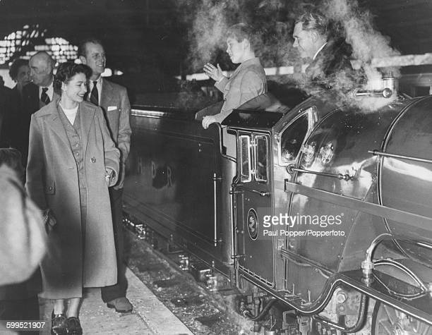 Queen Elizabeth II and Prince Philip Duke of Edinburgh are greeted by Prince Charles who is standing on the footplate of the narrow guage steam...