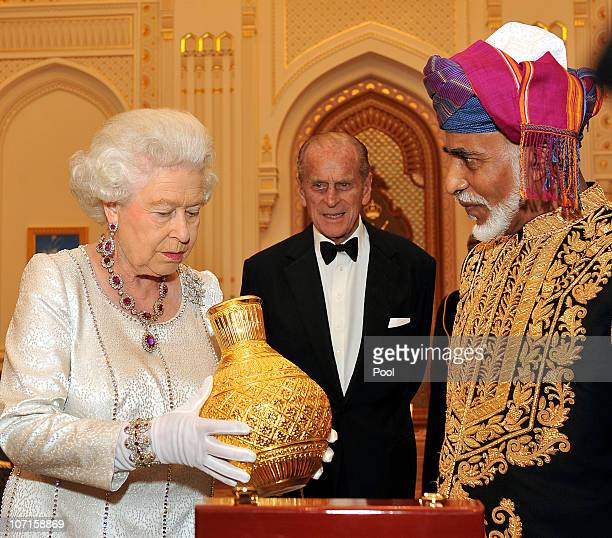 Queen Elizabeth II and Prince Philip Duke of Edinburgh are presented a golden vase by the Sultan of Oman before a State Banquet at his Palace on...