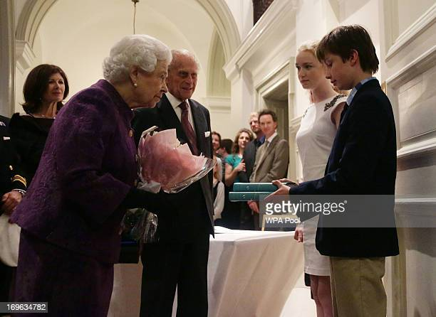 Queen Elizabeth II and Prince Philip Duke of Edinburgh are presented with copies of books by relatives of members of the 1953 Everest expedition...