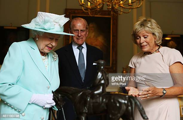 Queen Elizabeth II and Prince Philip Duke of Edinburgh are shown a piece by French sculptor PierreJules Mene of the 1863 Derby winner Macaroni by...