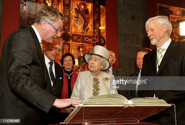Queen Elizabeth II and Prince Philip, Duke of Edinburgh are shown the Book of Kells during a visit to Trinity College Dublin on May 17, 2011 in...