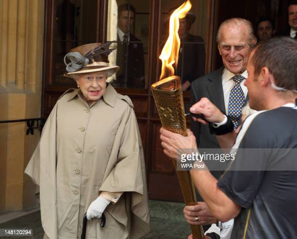Queen Elizabeth II and Prince Philip Duke of Edinburgh are shown the Olympic flame at Windsor Castle on day 53 of the London 2012 Olympic Torch Relay...