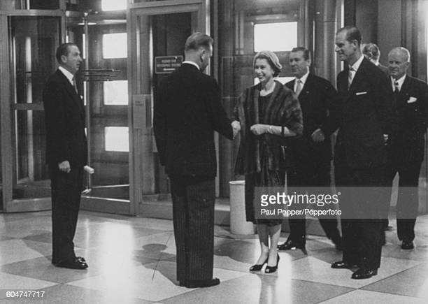 Queen Elizabeth II and Prince Philip Duke of Edinburgh are welcomed by United Nations Secretary General Dag Hammarskjold during a visit to the United...