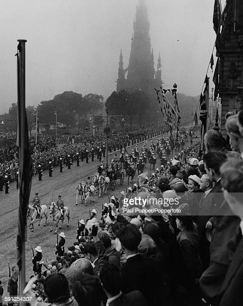 Queen Elizabeth II and Prince Philip Duke of Edinburgh drive in a carriage along Princes Street in a large procession in front of crowds of...