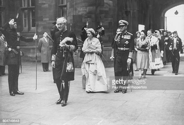 Queen Elizabeth II and Prince Philip Duke of Edinburgh follow John Maclay 1st Viscount Muirshiel the Secretary of State for Scotland as they cross...