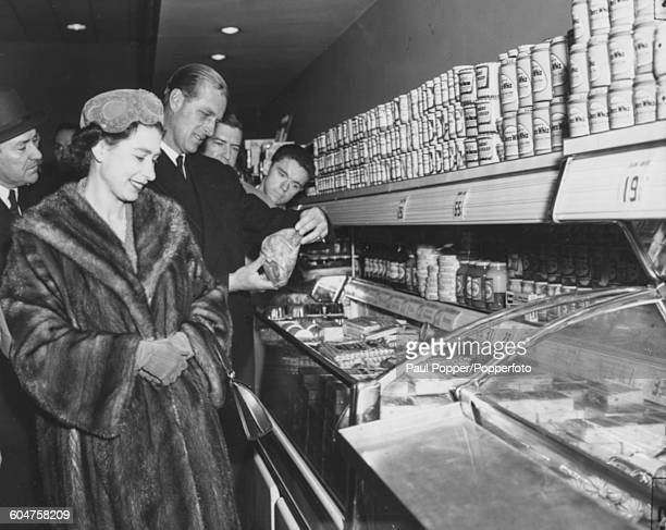 Queen Elizabeth II and Prince Philip Duke of Edinburgh inspect produce at a frozen meat centre inside a supermarket at the Giant Food Shopping Center...
