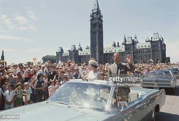 Queen Elizabeth II and Prince Philip Duke of Edinburgh pictured standing and waving from the rear seating area of an open top Lincoln Continental car...